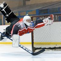Goalie marcus claesson making a spectacular save at an international ice hockey cup game